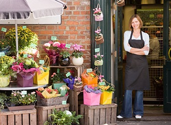 woman small business owner stands in the doorway to her flower shop